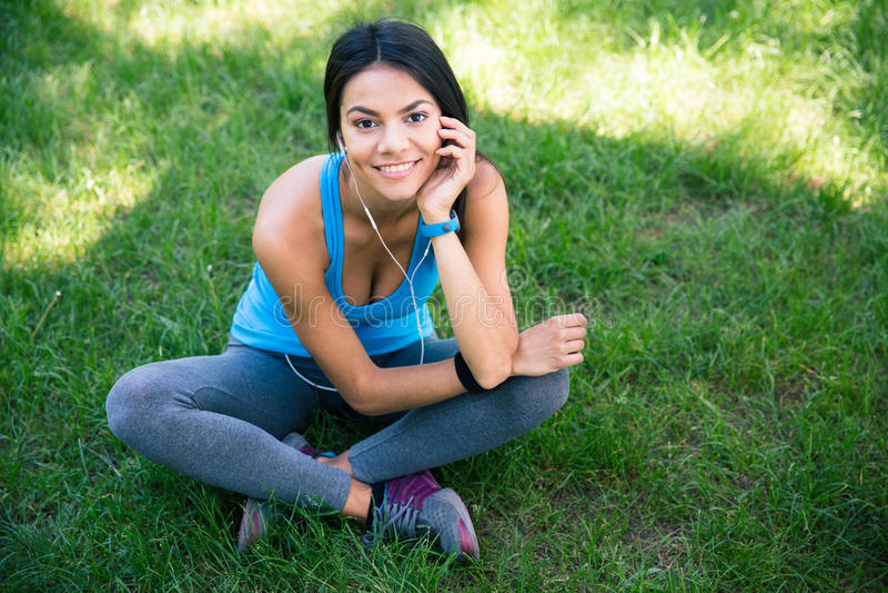 Femme de sourire de forme physique s'asseyant sur l'herbe verte photographie stock libre de droits