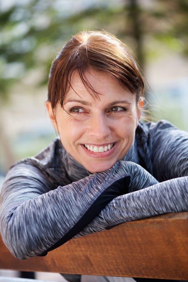 Femme de sourire de sports s'asseyant dehors image libre de droits