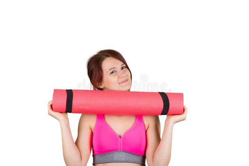 Femme de sourire en bonne santé d'ajustement sportif la belle, fille principale rouge tient une pomme et un tapis de yoga images libres de droits