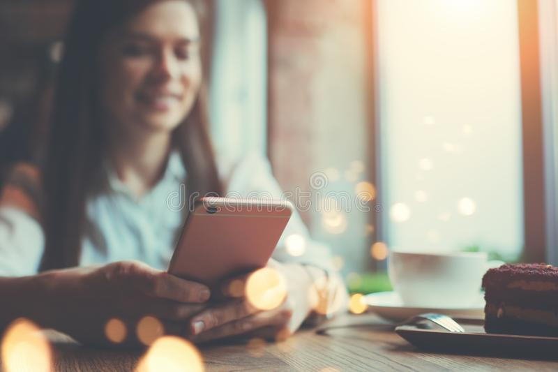 Femme de sourire en café avec le smartphone dans des mains et textoter dans les réseaux sociaux, seul se reposant image stock