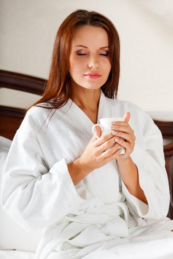 Femme de sourire en café potable de chambre à coucher sur le lit photos libres de droits