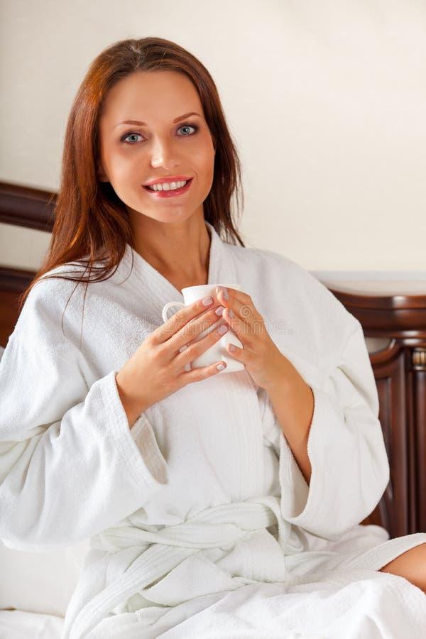 Femme de sourire en café potable de chambre à coucher sur le lit photo stock