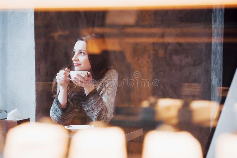 Femme de sourire en café utilisant le téléphone portable et textoter dans les réseaux sociaux, seul se reposant images libres de droits