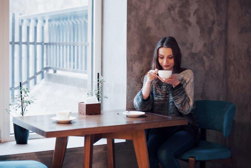 Femme de sourire en café utilisant le téléphone portable et textoter dans les réseaux sociaux, seul se reposant image libre de droits