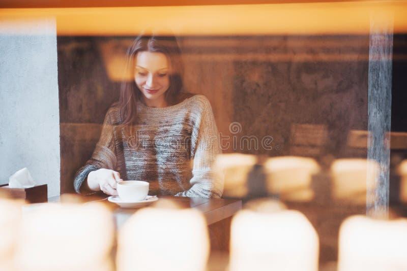 Femme de sourire en café utilisant le téléphone portable et textoter dans les réseaux sociaux, seul se reposant images stock