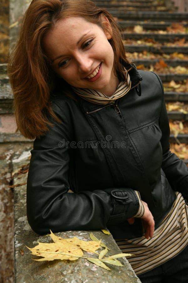 Femme de sourire en stationnement d'automne photographie stock libre de droits