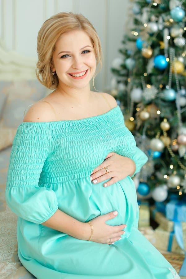 Femme de sourire enceinte portant la robe bleue étreignant le ventre et se reposant près de l'arbre et des présents de Noël image stock