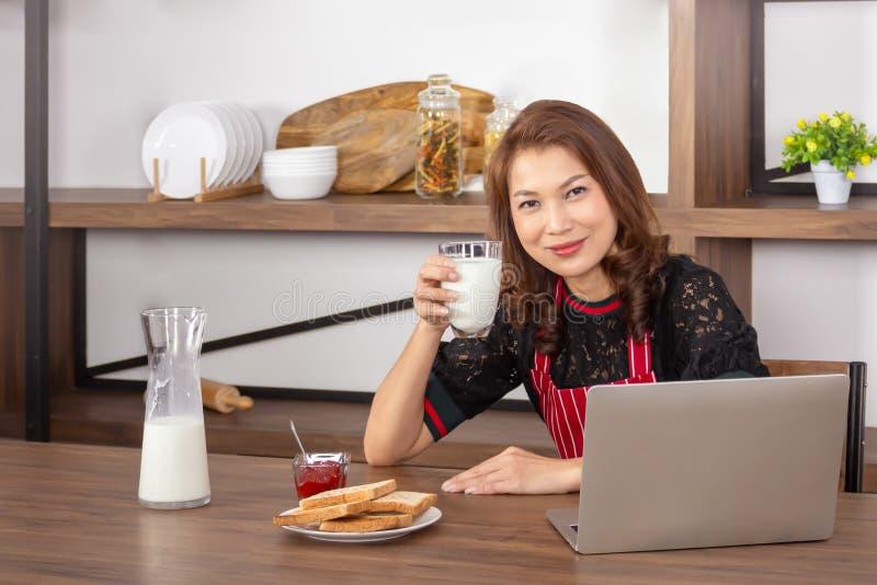 Femme de sourire et tenir un verre de lait image stock