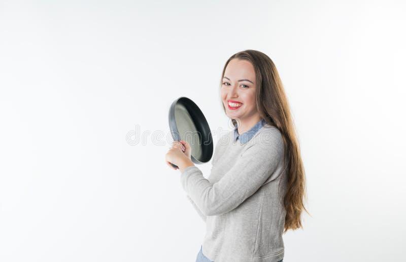 Femme de sourire fâchée avec le rire d'insulte sur son visage et poêle photo libre de droits