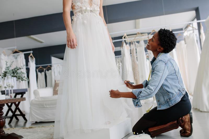 Femme de sourire faisant l'ajustement à la robe de mariée images libres de droits