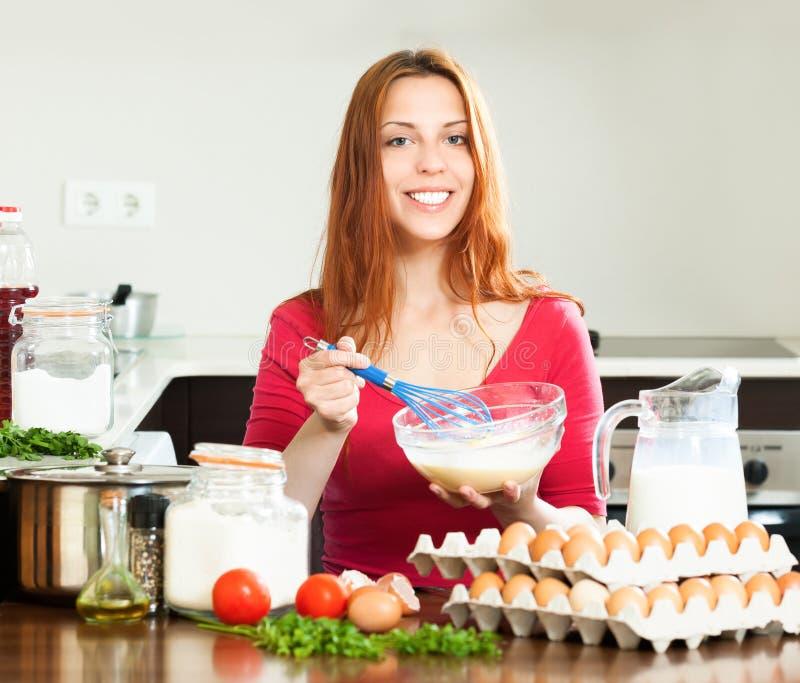 Femme de sourire faisant la pâte ou l'omlet image stock