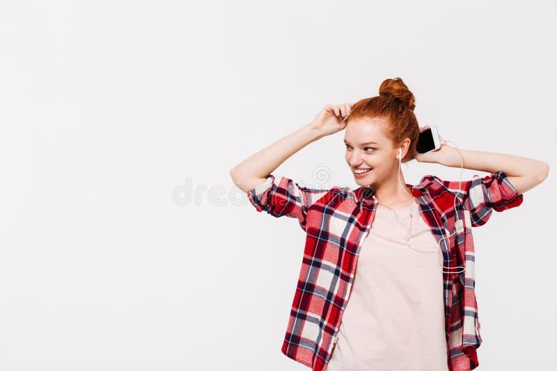 Femme de sourire de gingembre dans la musique de écoute de chemise et d'écouteurs photographie stock libre de droits