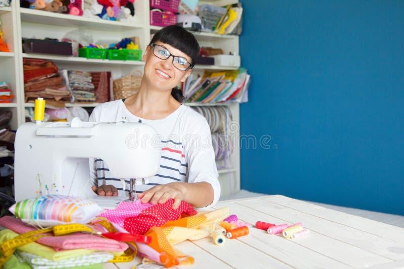 Femme de sourire heureuse à côté d'une machine à coudre Tissu, fil et photos libres de droits