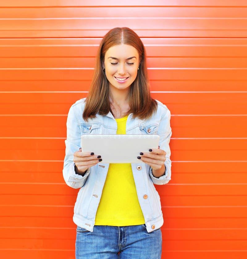Femme de sourire heureuse à l'aide de l'ordinateur de PC de comprimé dans la ville au-dessus de l'orange photographie stock libre de droits