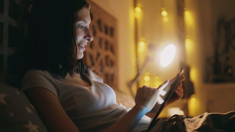 Femme de sourire heureuse à l'aide de la tablette pour partager le media social se trouvant dans le lit à la maison la nuit images libres de droits