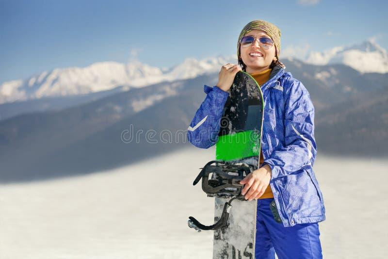 Femme de sourire heureuse avec le surf des neiges sur la colline de montagne photo libre de droits