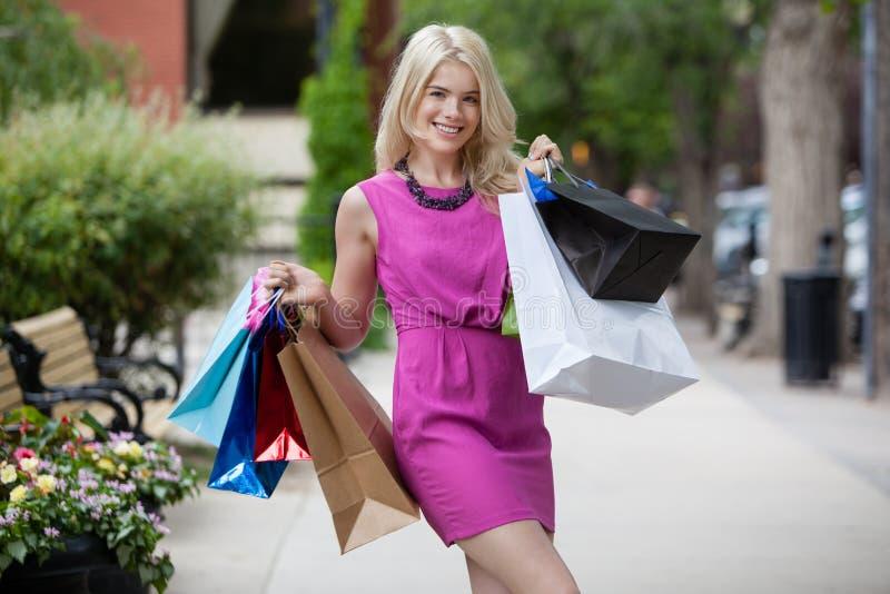 Femme de sourire heureuse d'achats photos stock