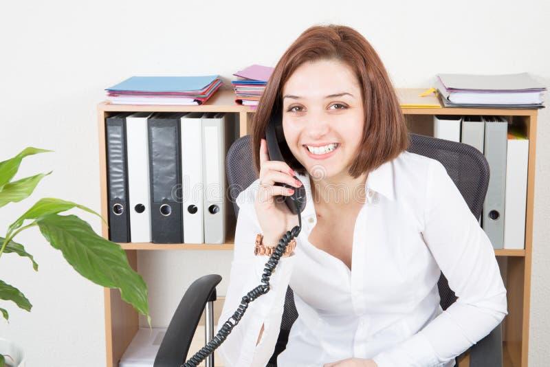 Femme de sourire heureuse d'affaires avec le téléphone dans le bureau dans le concept de communication images libres de droits