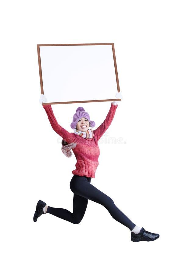 Femme de sourire heureuse dans l'habillement d'hiver tenant le conseil vide - d'isolement images stock