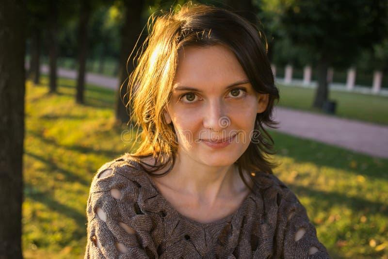 Femme de sourire heureuse en parc l'été arrière d'or de coucher du soleil d'éclairage photo libre de droits
