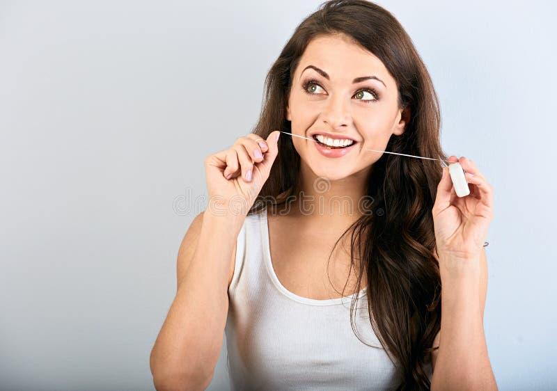 Femme de sourire heureuse nettoyant les dents le fil dentaire sur le fond bleu avec l'espace vide Hygi?ne dentaire image libre de droits