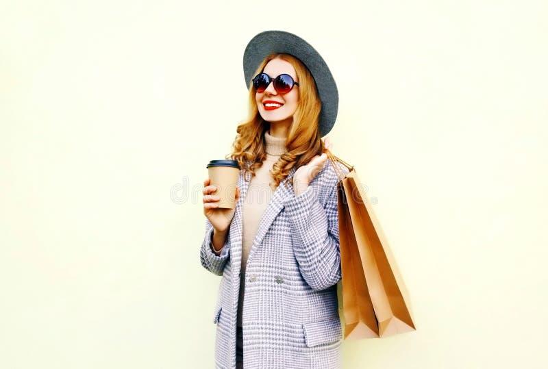 Femme de sourire heureuse de portrait avec des sacs à provisions, tenant la tasse de café, manteau rose de port, chapeau rond photographie stock libre de droits