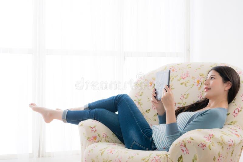 Femme de sourire heureuse se couchant sur la chaise de sofa images libres de droits