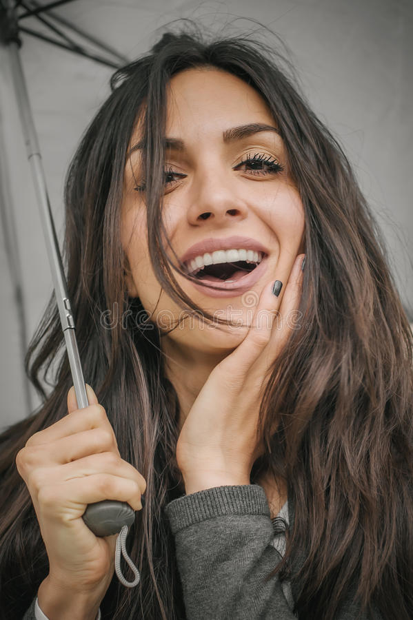 Femme de sourire heureuse sous le parapluie sous la pluie photos stock