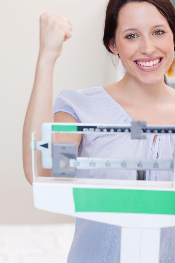 Femme de sourire heureuse sur l'échelle images stock