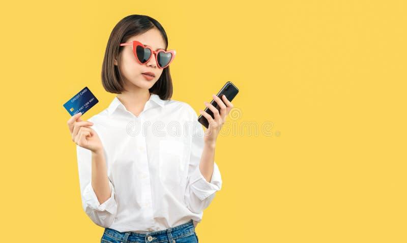 Femme de sourire heureuse tenant le téléphone et la carte de crédit futés avec des achats en ligne image libre de droits