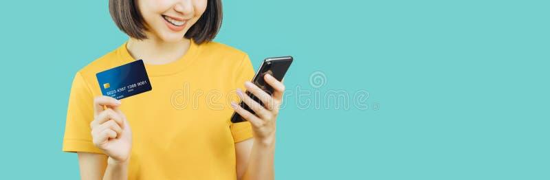 Femme de sourire heureuse tenant le t?l?phone et la carte de cr?dit fut?s photos stock