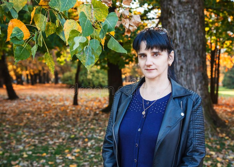 Femme de sourire de jeune brune sur une promenade en parc photo stock