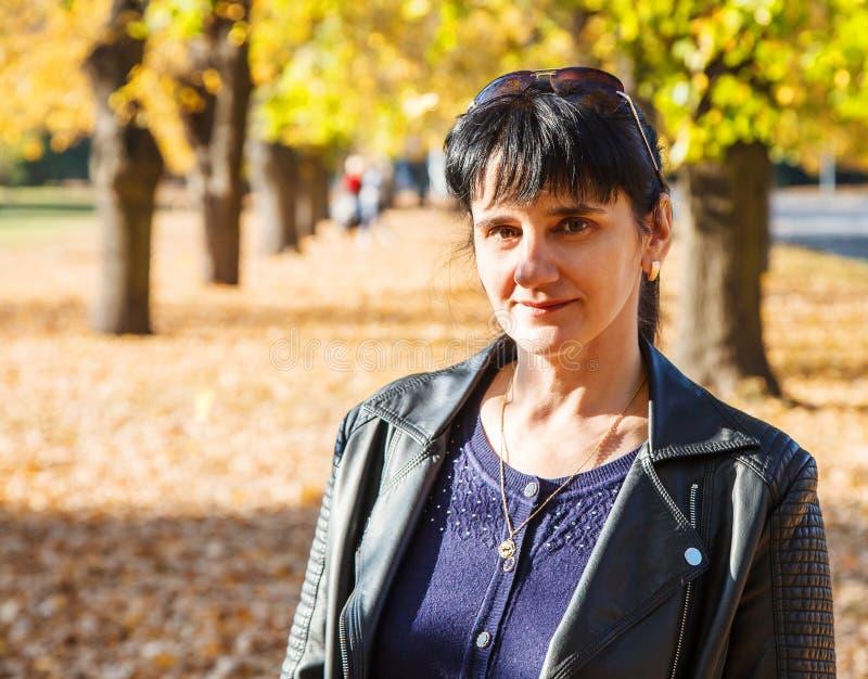 Femme de sourire de jeune brune sur une promenade en parc photographie stock libre de droits