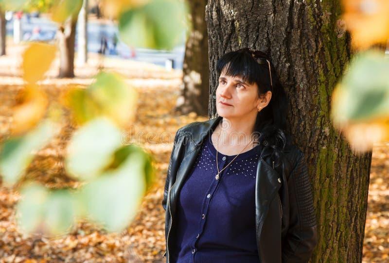 Femme de sourire de jeune brune sur une promenade en parc images stock