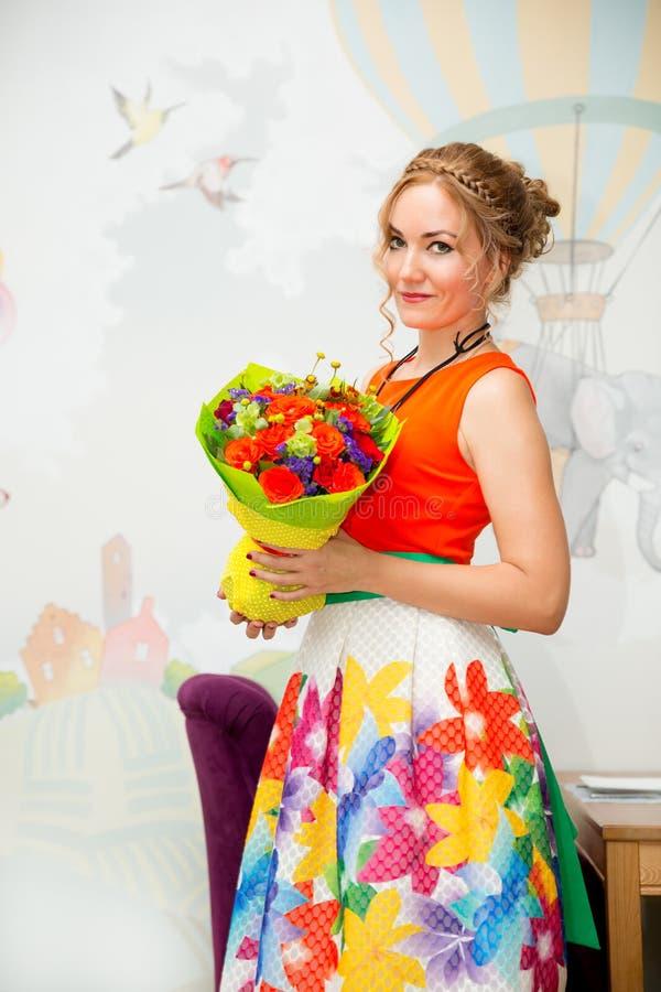 Femme de sourire de jeunes belle avec un bouquet des fleurs à l'anniversaire Portrait dans un café photo stock