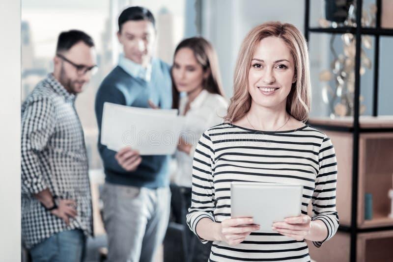 Femme de sourire joyeuse tenant l'ordinateur portable et se sentant bien elle-même image libre de droits