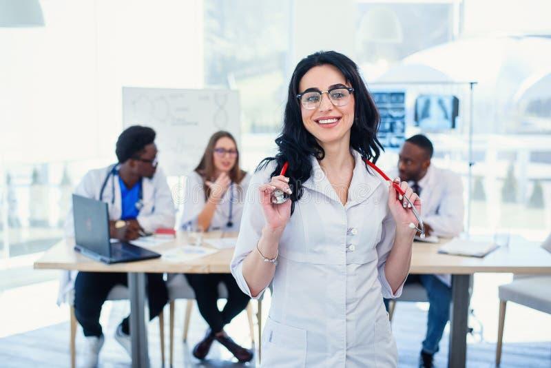 Femme de sourire de médecin avec la position de stéthoscope devant l'équipe de médecin à l'hôpital Jeune femelle attirante photos libres de droits