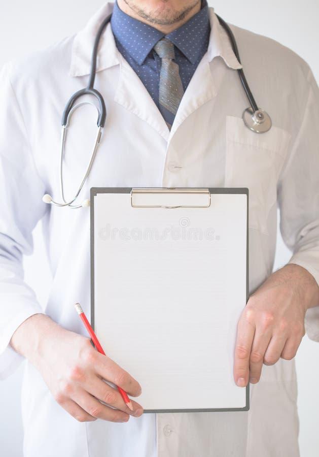 Femme de sourire de médecin tenant le presse-papiers vide dans des mains sur le blanc photographie stock libre de droits