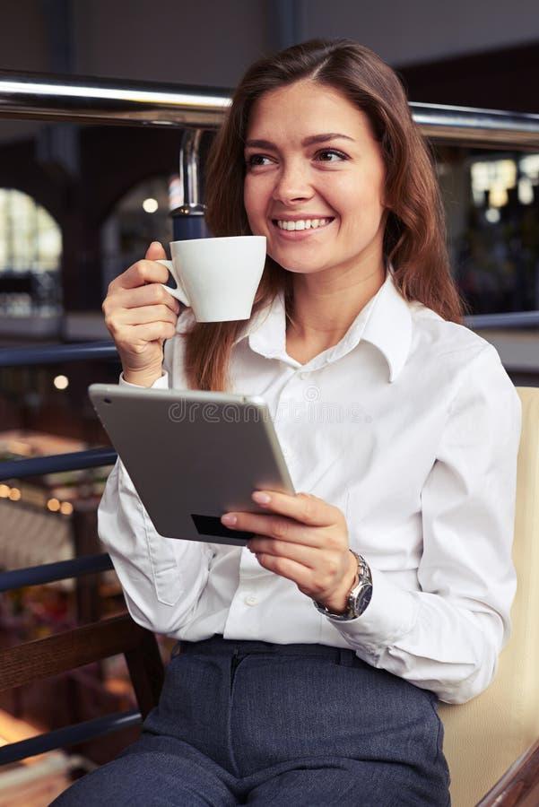 Femme de sourire magnifique d'affaires appréciant la tasse de café savoureuse images libres de droits
