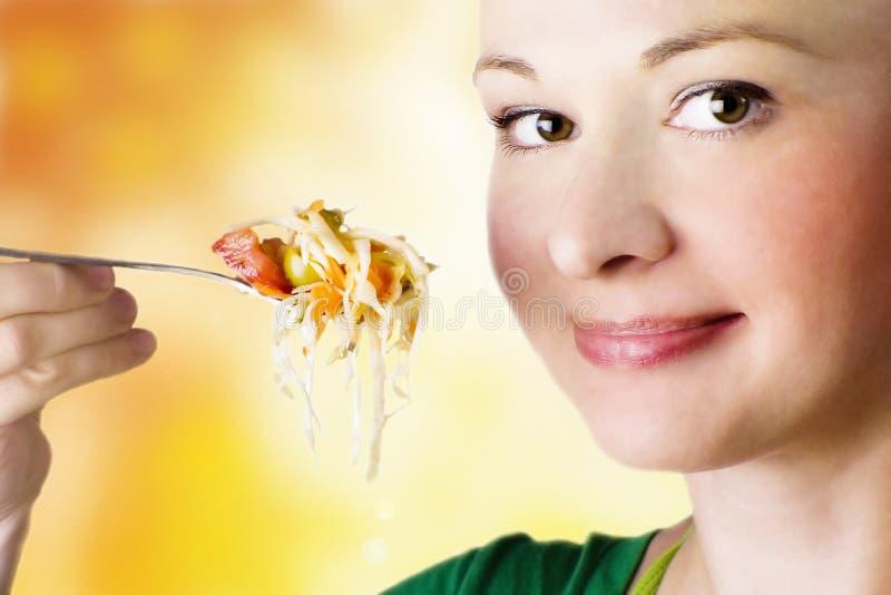 Femme de sourire mangeant de la salade photos stock