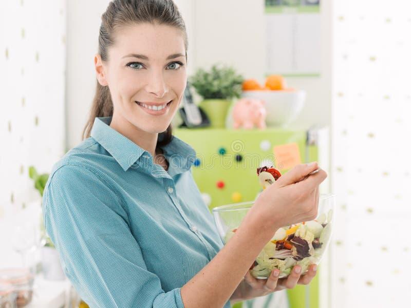 Femme de sourire mangeant de la salade dans la cuisine photographie stock libre de droits