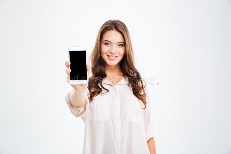 Femme de sourire montrant l'écran vide de smartphone d'isolement sur le fond blanc images libres de droits
