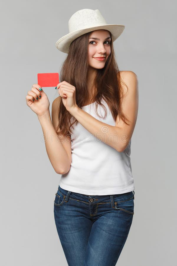 Femme de sourire montrant la carte de crédit en blanc dans le T-shirt blanc, d'isolement au-dessus du fond gris image stock