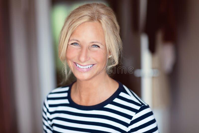 femme de sourire moyenne d'âge Elle est à la maison Dans une chambre à coucher utilisant un chandail rayé photo libre de droits