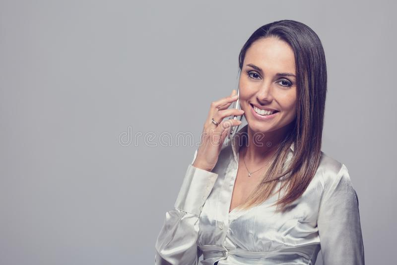 Femme de sourire parlant sur le smartphone photos stock