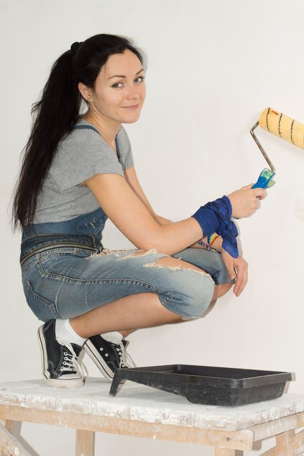 Femme de sourire peignant le mur de sa maison photographie stock libre de droits