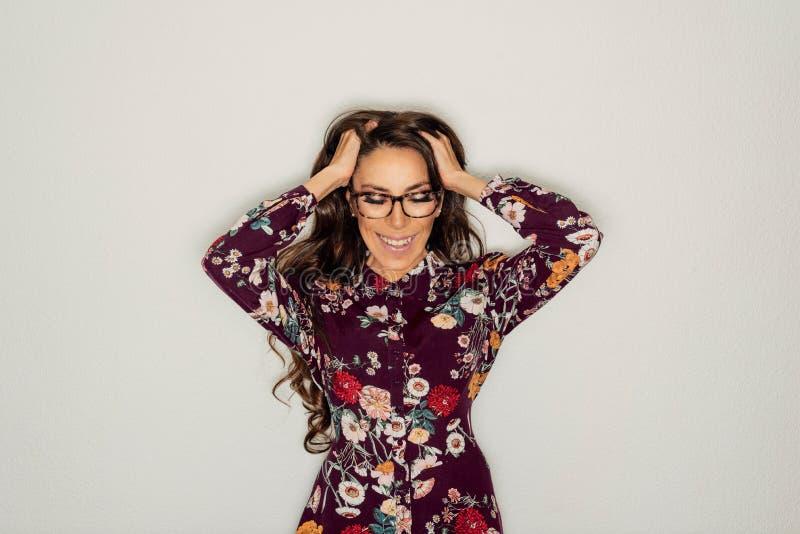 Femme de sourire portant la robe florale, avec les verres et les mains gradués sur la tête photo libre de droits
