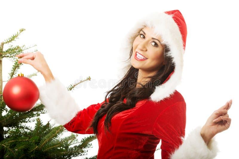 Femme de sourire portant le père noël décorant l'arbre de Noël image libre de droits