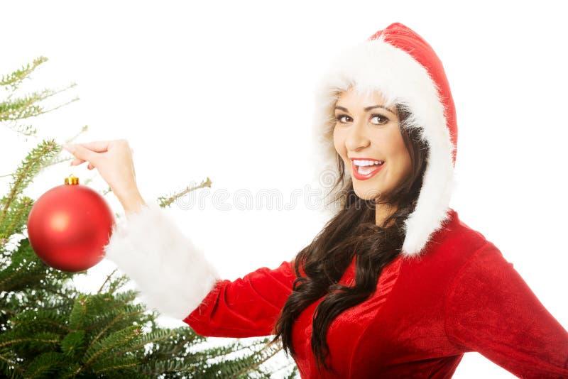 Femme de sourire portant le père noël décorant l'arbre de Noël images stock