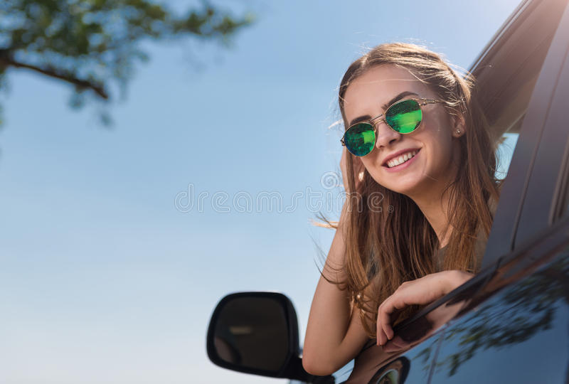 Femme de sourire positive regardant hors de la voiture photos stock